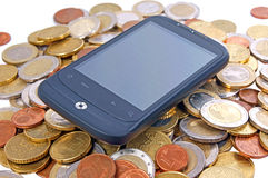 Smartphone. Black smartphone and many coins Stock Image