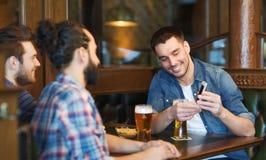 Αρσενικοί φίλοι με την μπύρα κατανάλωσης smartphone στο φραγμό Στοκ εικόνα με δικαίωμα ελεύθερης χρήσης