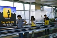 Люди проверяя smartphone на авиапорте Стоковые Изображения RF