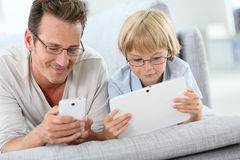 Отец и сын играя с smartphone и таблеткой Стоковая Фотография