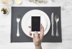 Smartphone above diner setting Royalty Free Stock Photography