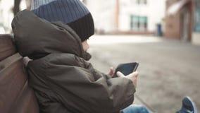 Smartphone aditivo do rapaz pequeno que senta-se no banco na rua da cidade Criança bonito do bebê com telefone celular no banco e filme