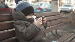 Smartphone aditivo do rapaz pequeno que senta-se no banco na rua da cidade Criança bonito do bebê com telefone celular no banco e vídeos de arquivo