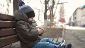 Smartphone aditivo do rapaz pequeno que senta-se no banco na rua da cidade Crian?a bonito do beb? com telefone celular no banco e video estoque