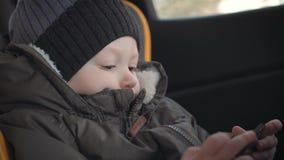Smartphone aditivo do rapaz pequeno que senta-se no banco na rua da cidade Crian?a bonito do beb? com telefone celular no banco e vídeos de arquivo