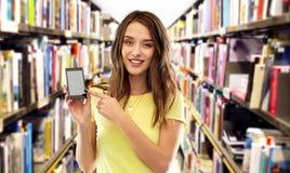 Smartphone adolescent d'apparence de fille d'étudiant à la bibliothèque photo stock
