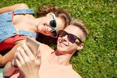Smartphone adolescent heureux de couples se trouvant sur l'herbe Photographie stock