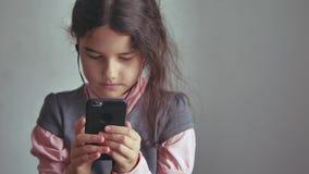 Smartphone adolescente de la muchacha que escucha la música en su el teléfono con los auriculares interiores Imágenes de archivo libres de regalías