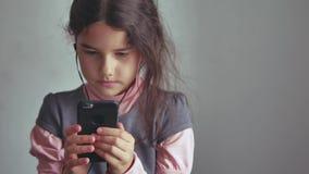 Smartphone adolescente de la muchacha que escucha la música en su el teléfono con los auriculares interiores Fotos de archivo libres de regalías
