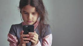 Smartphone adolescente de la muchacha que escucha la música en su teléfono con los auriculares interiores Fotografía de archivo libre de regalías