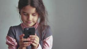 Smartphone adolescente de la muchacha que escucha la música en su teléfono con los auriculares interiores Imagen de archivo