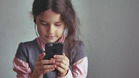 Smartphone adolescente de la muchacha que escucha la música en su teléfono con los auriculares interiores Imagen de archivo libre de regalías