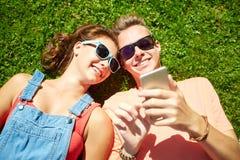 Smartphone adolescente feliz de los pares que miente en hierba Fotografía de archivo