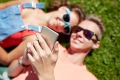 Smartphone adolescente feliz de los pares que miente en hierba Imagen de archivo
