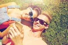 Smartphone adolescente feliz de los pares que miente en hierba Imagenes de archivo