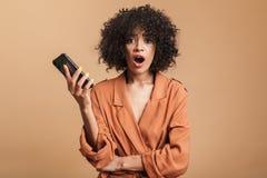 Smartphone africano bonito chocado de la tenencia de la mujer y mirada de la cámara imagen de archivo libre de regalías