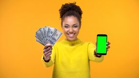 Smartphone afro-americano da exibi??o da mulher e grupo dos d?lares, transfer?ncia de dinheiro fotografia de stock royalty free
