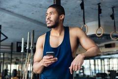 Smartphone afro-americano do holdind do indivíduo do halterofilista foto de stock