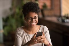 Smartphone afro-americano milenar feliz da terra arrendada da mulher usando apps do comércio eletrónico fotografia de stock royalty free
