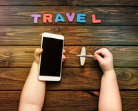 Smartphone and airplane in the hands of a child, travel against the background of a wooden table. stock photo