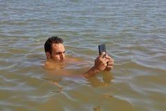 Smartphone alla spiaggia fotografia stock
