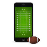 Smartphone with american football ball and field on the screen. Stock Image