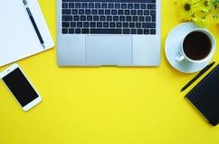 Smartphone, anmärkning, blommor, kaffe, panna och bärbar dator på gul bakgrund kopiera avstånd fotografering för bildbyråer
