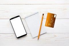 Smartphone, anteckningsbok, blyertspenna och kreditkort på en vit tabell Royaltyfri Fotografi
