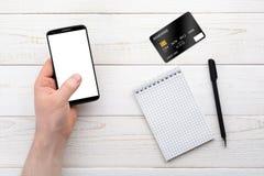 Smartphone, anteckningsbok, penna och kreditkort på en vit tabell Arkivfoto