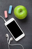 Smartphone and apple on blackboard background Royalty Free Stock Photos