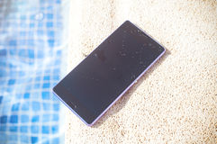 Smartphone around the pool Royalty Free Stock Photo