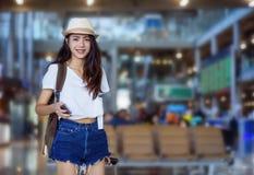 Smartphone asiático de la tenencia de la mujer en el aeropuerto imagenes de archivo