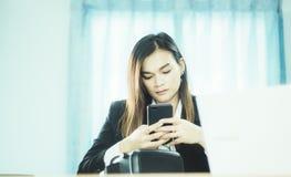 Smartphone asiático del control de la mujer de negocios, con el documento las ventas de las auriculares de VR en el mercado mundi fotos de archivo libres de regalías