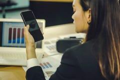 Smartphone asiático del control de la mujer de negocios de la vista posterior, con el documento las ventas de las auriculares de  fotografía de archivo