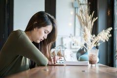 Smartphone asiático del uso de la mujer del primer para las noticias en línea leídas en el escritorio contrario de madera en cafe Foto de archivo libre de regalías