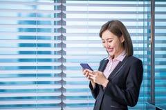 Smartphone asiático do uso da mulher de negócio imagem de stock royalty free