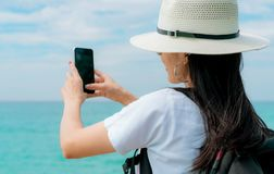Smartphone asiático novo do uso do chapéu do desgaste de mulher do mochileiro que toma o selfie no cais Férias de verão na praia  fotografia de stock royalty free