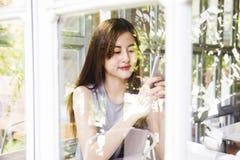 Smartphone asiatico di uso delle donne nel negozio del caffè Immagini Stock Libere da Diritti