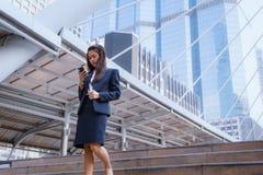 Smartphone asiatique de position et d'utilisation de femme d'affaires avec les affaires b images stock