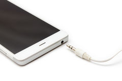 Smartphone and Audio Cable Disconnected. Mini audio cable disconnected from the smartphone. White background isolated royalty free stock photo