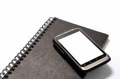 Smartphone auf Anmerkungsbuch Stockfotos