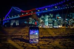 Smartphone auf Boden nehmendem Foto der Stadt in den Lichtern stockbilder