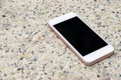 Smartphone auf dem Kies, Stockfotografie