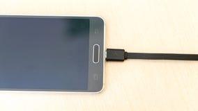 Smartphone auf der Aufladung Stockfoto