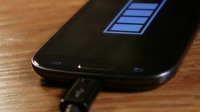 Smartphone auf der Aufladung in der Rotation stock video
