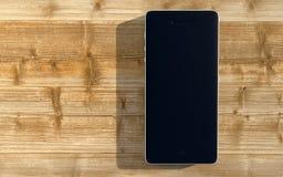 Smartphone auf einem hölzernen Schreibtisch lizenzfreie abbildung