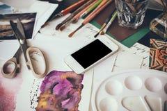 Smartphone auf einer Tabelle im Künstlerstudio Stockfotografie