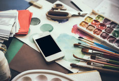 Smartphone auf einer Tabelle im Künstlerstudio Stockbilder