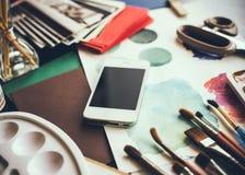Smartphone auf einer Tabelle im Künstlerstudio Stockfotos