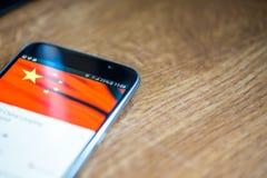 Smartphone auf hölzernem Hintergrund mit Zeichen des Netzes 5G 25-Prozent-Gebühr und China-Flagge auf dem Schirm Lizenzfreie Stockbilder